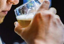 man smelling beer